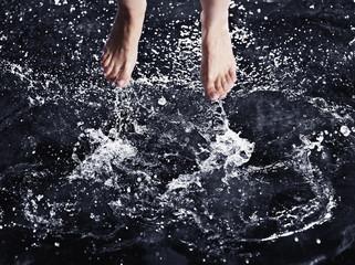 Bare feet splashing in water