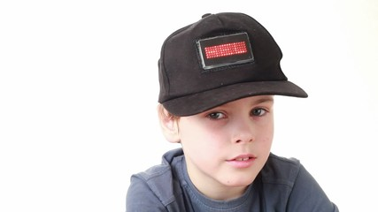 boy in cap with word Hello onLED display grieves