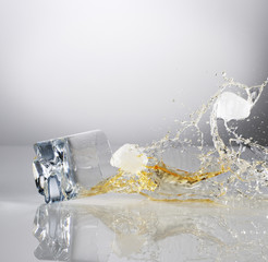 Alcohol and ice cubes spilling from falling highball glass