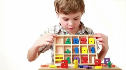 boy raises box with cells containing figures and shows equation