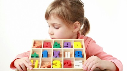 girl holds box with cells and looks at multicolor figures in it