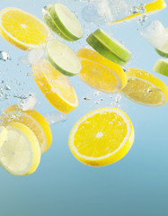 Close up of sliced lemons and limes splashing in water