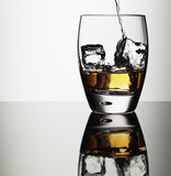 Alcohol pouring into highball glass with ice cubes