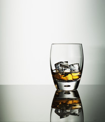 Highball glass of alcohol with ice cubes