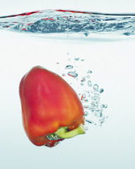 Close up of red bell pepper splashing in water