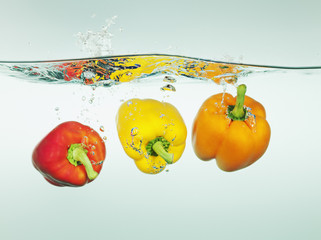Bell peppers splashing in water
