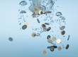 Euro coins splashing in water