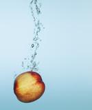 Peach splashing in water