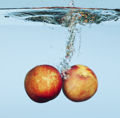 Close up of Peaches splashing in water