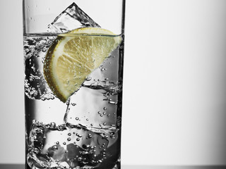 """""""Close up of glass with water, ice cubes and lemon slice"""""""