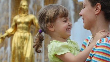 Mother and daughter smile near Fountain Friendship of Peoples