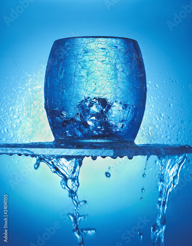 """Close up of blue glass, ice cubes and dripping water"""
