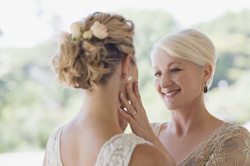 Mother touching bride?s face