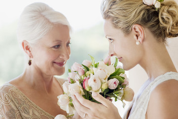 Mother and bride smelling bouquet