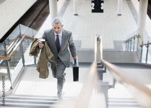 Businessman walking up stairs in train station