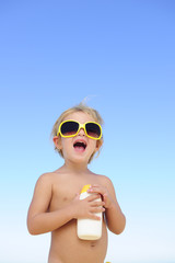 child with sunglasses holding suncream