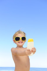 child with sunglasses showing suncream