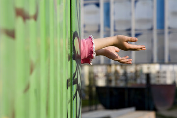 hands of little girl and metal fence