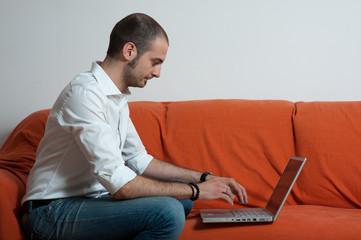 uomo seduto su divano arancione che lavora al computer