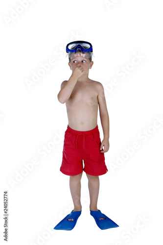 Young boy in swimsuit and snorkeling gear holding his nose
