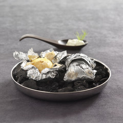 potatoes with horseradish sauce cooked in aluminium foil on coals