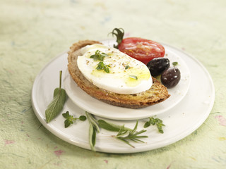 mozzarella with herbs on toast with tomato and olives