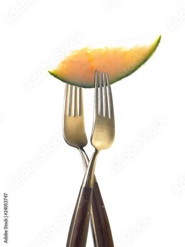 two forks with slice of melon