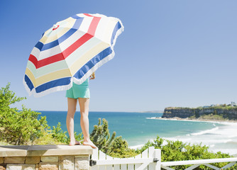 woman holding umbrella near ocean
