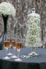 baby's breath under a glass dome and glasses of pink champagne