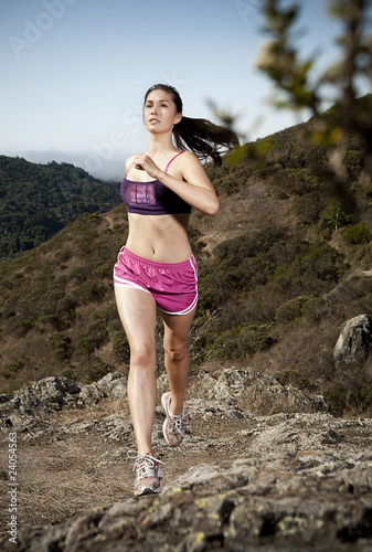 Athletic woman running on hill