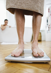 Man weighing himself on bathroom scales