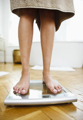 Woman weighing herself on bathroom scales