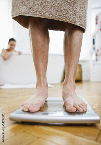 Man weighing himself on bathroom scales