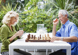 Couple playing chess outdoors