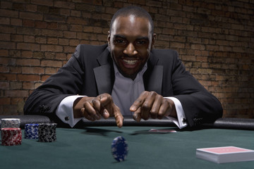 Man rolling poker chip in casino