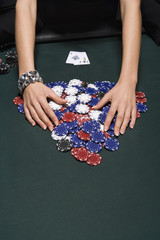 Woman gathering poker chips in casino