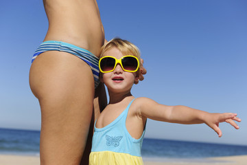 Mother and daughter with sunglasses on the beach