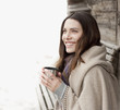 Woman wrapped in blanket drinking coffee