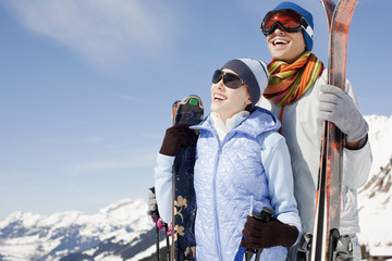 Couple standing with skis on mountain top
