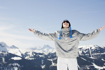Woman with arms outstretched on mountain top
