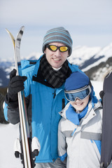 Father and son holding skis