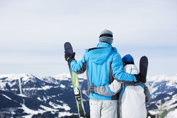 Father and son holding skis on mountain top