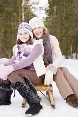 Mother and daughter sitting on sled in snow