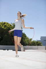 Woman skipping rope in urban plaza