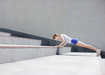 Woman doing push-ups on urban stairs