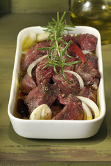 raw beef marinating in olive oil