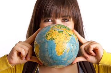 Frau hält Globus zwischen den Fingern