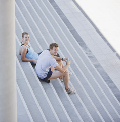 Couple resting on stairs after exercise