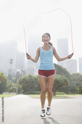 Woman skipping rope in urban park