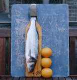 bass on chopping board with oranges